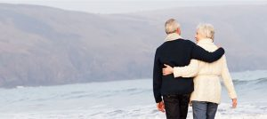 Image of retired couple walking down beach