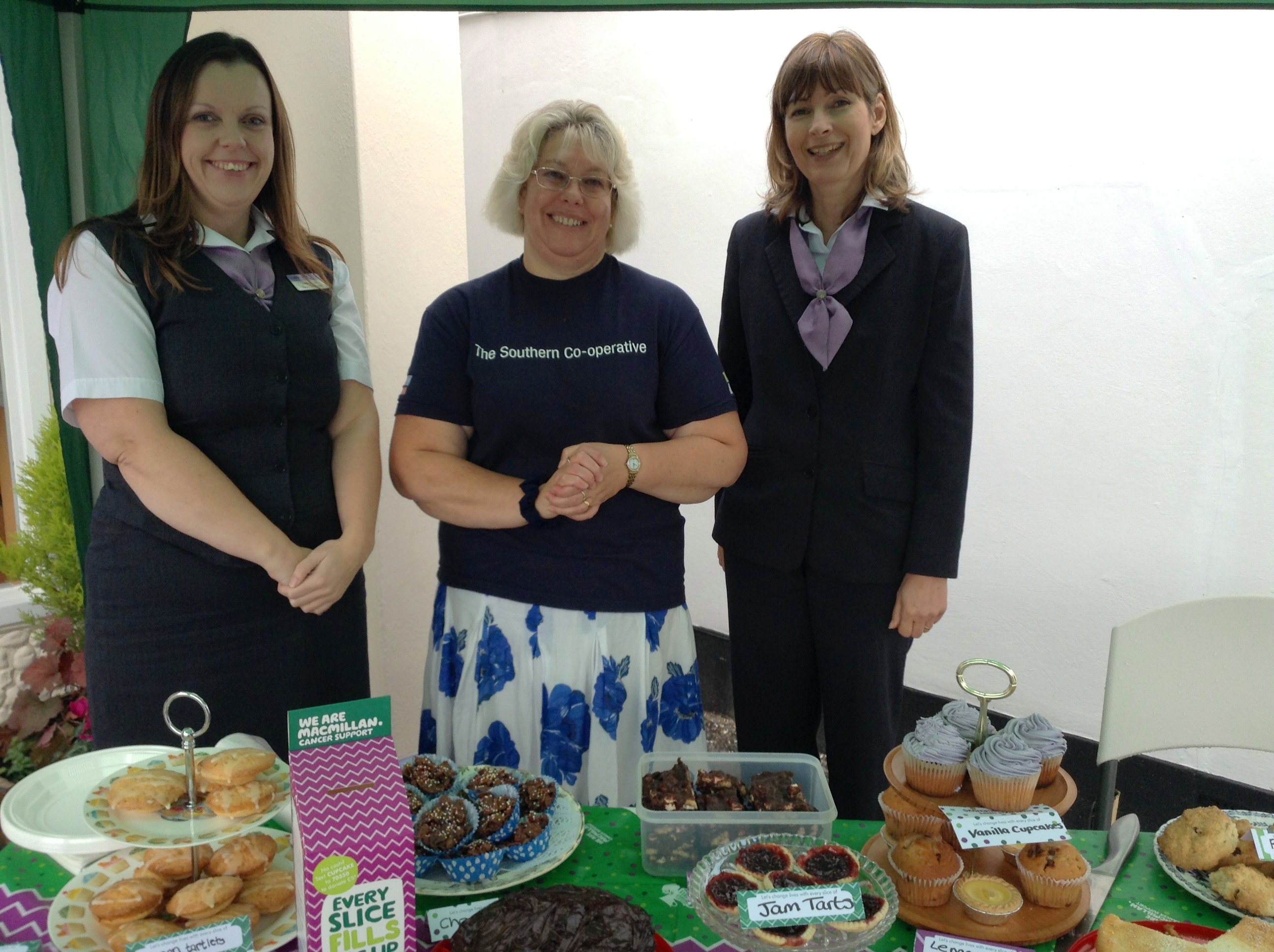 Image of The Southern Co-operative Funeralcare Co-ordinators (L-R) Shirley Heaton, Lindsey Booker and Julie Sells with a selection of home-made cakes as part of their Macmillan Coffee and Cake sale.